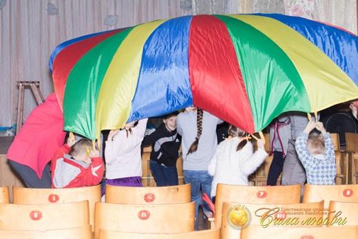 Игра с парашютом в детском клубе фотография