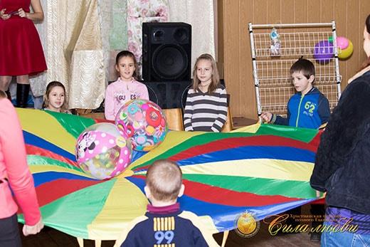 Ребята весело играли с парашютом фотография
